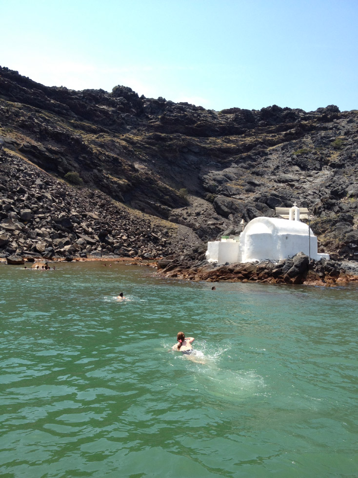 Swimmers brave the cold Aegean waters en route to the volcano's warm springs